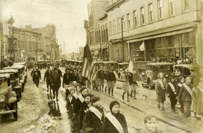 A parade was held for the dedication of Memorial Bridge photo shows children with sashes walking down the street as spectators watch from the sidewalk